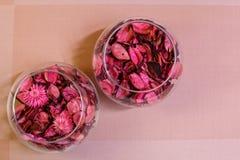 Floreros en la tabla con los pétalos color de rosa, visión superior foto de archivo