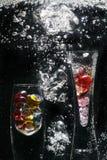 Floreros y guijarros de cristal en agua Imágenes de archivo libres de regalías