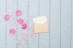 Floresça as pétalas e o cartão no envelope do porte postal do vintage Fotografia de Stock