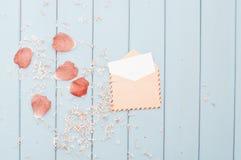 Floresça as pétalas e o cartão no envelope do porte postal do vintage Foto de Stock