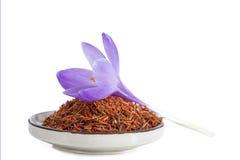 Floresça o açafrão e a especiaria secada do açafrão em uma bacia no fundo branco Fotografia de Stock
