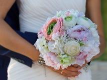 Floresça o bouqet nas mãos da noiva que preparam o abraço Imagens de Stock