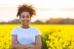Flores afro-americanos felizes do amarelo da mulher do adolescente da raça misturada Fotografia de Stock Royalty Free