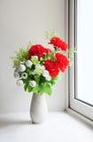 Flores al lado de la ventana Fotos de archivo libres de regalías