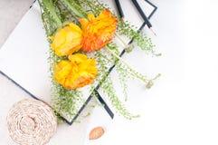 Flores amarelas, cestas de vime e um caderno Foto de Stock