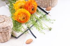 Flores amarelas, cestas de vime e um caderno Imagens de Stock