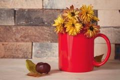 Flores amarelas no copo vermelho na mesa de cozinha Fotos de Stock