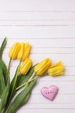 Flores amarillas aromáticas frescas de los tulipanes y corazón rosado decorativo foto de archivo libre de regalías