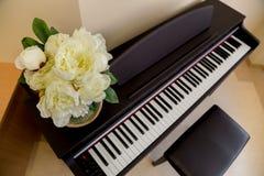 Flores amarillas encima del piano de madera negro en sala de clase foto de archivo libre de regalías