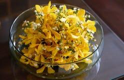 Flores amarillas que flotan en florero del bol de vidrio en la tabla superior de cristal adentro foto de archivo