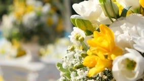 Flores amarillas y blancas en los floreros decorativos para adornar la yarda para la ceremonia de boda almacen de metraje de vídeo