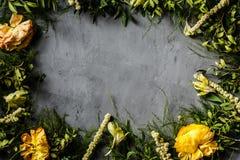 Flores amarillas y hojas verdes que mienten en fondo concreto gris Decoración para las mujeres día, fondo del día de la madre pla fotografía de archivo