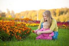 Flores anaranjadas de la demostración de la mujer en cama al bebé lindo Foto de archivo