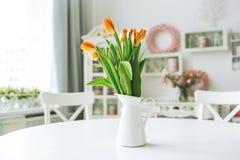 Flores anaranjadas hermosas en florero en la tabla de cocina rústica Fotografía de archivo libre de regalías
