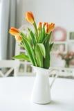 Flores anaranjadas hermosas en florero en la tabla de cocina rústica Fotos de archivo