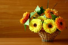 Flores artificiais decorativas brilhantes em uma cesta tecida para seu desktop imagens de stock