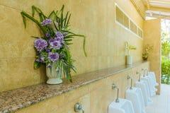 Flores artificiais em uns potenciômetros para a decoração colocada na prateleira fotos de stock royalty free