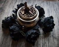 Flores artificiais pretas com queimador de incenso Fotos de Stock