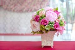Flores artificiales coloridas hechas del paño en un florero de cerámica rectangular Imágenes de archivo libres de regalías