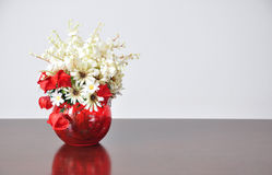 Flores artificiales de los floreros en el escritorio Imagenes de archivo