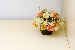 Flores artificiales en la tabla de madera Fotografía de archivo libre de regalías