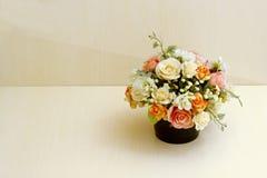 Flores artificiales en la tabla de madera Foto de archivo libre de regalías