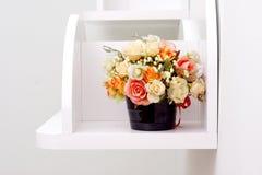 Flores artificiales en los estantes de madera blancos Fotos de archivo