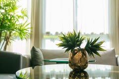 Flores artificiales en un florero en una tabla en la sala de estar Fotografía de archivo libre de regalías