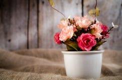 Flores artificiales y pote blanco Fotografía de archivo