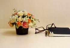 Flores artificiales y sistema de la herramienta de la oficina en el blackgro de madera de la tabla Fotos de archivo libres de regalías