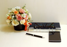 Flores artificiales y sistema de la herramienta de la oficina en el blackgro de madera de la tabla Imagen de archivo libre de regalías
