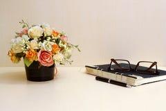 Flores artificiales y sistema de la herramienta de la oficina en el blackgro de madera de la tabla Foto de archivo