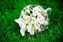 Flores blancas de la boda en la hierba verde Foto de archivo