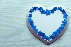 Flores blancas del corazón y de la luz de la porcelana presentadas en la forma de un corazón en una tabla de madera azul foto de archivo