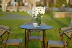 Flores blancas en el florero de cristal en la tabla de madera imagenes de archivo
