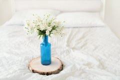 Flores blancas en maceta azul en cama Foto de archivo
