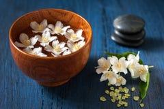 Flores blancas en un cuenco, piedras para el masaje y sal del mar. Composición del balneario. Fotografía de archivo libre de regalías