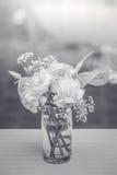 Flores blancas en un florero en la mesa de centro con un negro y un whi Fotografía de archivo