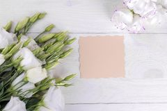 Flores blancas hermosas Eustoma con una forma de la inscripción en una tabla de madera blanca fotos de archivo libres de regalías