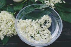 Flores blancas y hojas de la mentira de la baya del saúco en un cuenco en un fondo de madera rústico imagen de archivo libre de regalías