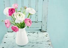 Flores blancas y rosadas en silla azul clara Imagen de archivo libre de regalías