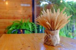 Flores bonitas da grama seca decoradas com estilo do vintage na tabela de madeira no café fotos de stock