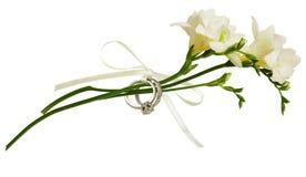 Flores brancas da frésia e dois anéis dourados amarrados com fita de seda imagem de stock royalty free