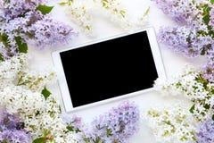 Flores brancas do tablet pc e do lilás no backgrou de madeira branco fotos de stock