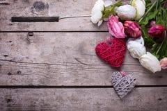 Flores brancas e cor-de-rosa e corações decorativos no vintage de madeira Foto de Stock