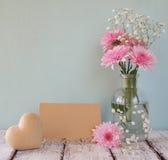Flores brancas e cor-de-rosa frescas, coração ao lado do cartão vazio do vintage sobre a tabela de madeira Fotos de Stock