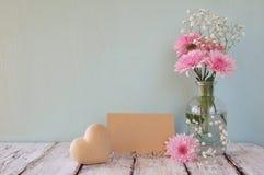 Flores brancas e cor-de-rosa frescas, coração ao lado do cartão vazio do vintage sobre a tabela de madeira Fotografia de Stock Royalty Free