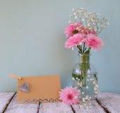 Flores brancas e cor-de-rosa frescas, coração ao lado do cartão vazio do vintage sobre a tabela de madeira Foto de Stock
