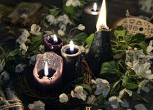 Flores brancas, velas pretas e objetos místicos imagem de stock