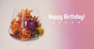 Flores color de rosa secadas adornadas tarjeta del feliz cumpleaños en la copa de vino, fondo violeta rosado de la pendiente Flor Imagenes de archivo